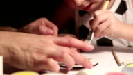 Boy works on his art project painting with a brush with his mother's help video