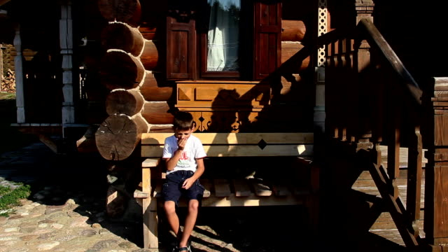 boy yawning, sleepy in the Russian village, background home from a bar video