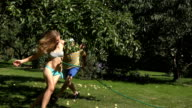 boyfriend catching and spraying girlfriend with water hose between apple tree branches. video