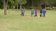 Boys and girls playing football in park video