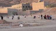 Boys and men playing soccer in the evening on a sand field in Tamegroute video