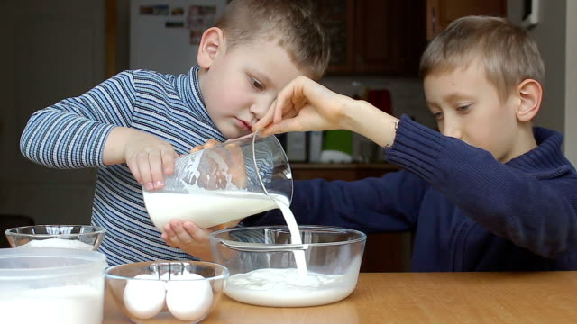 Boys are going to make pancackes and young pours the milk into a bowl video