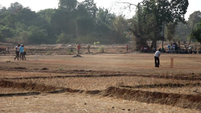 Boys are playing cricket on a field of village video