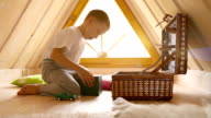 Boy's discovering the contents of the chest with toys in the attic video