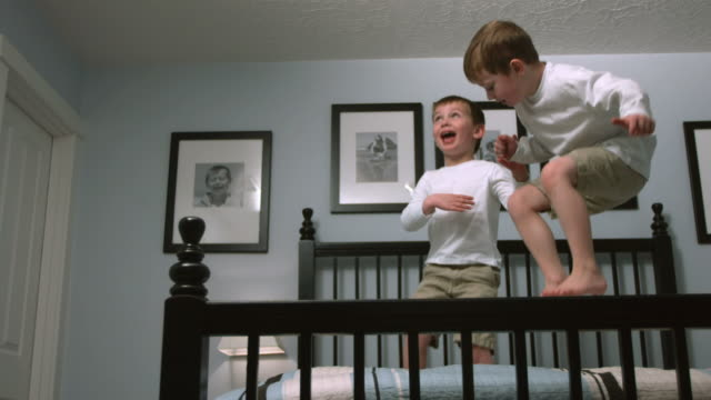 Boys jump on bed, slow motion video