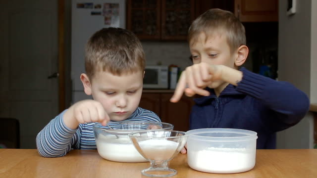 Boys prepare dough and older boy teaches younger video