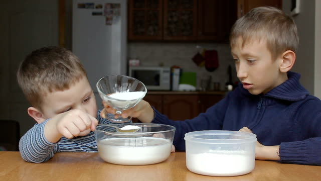 Boys prepare dough and younger boy add sugar video