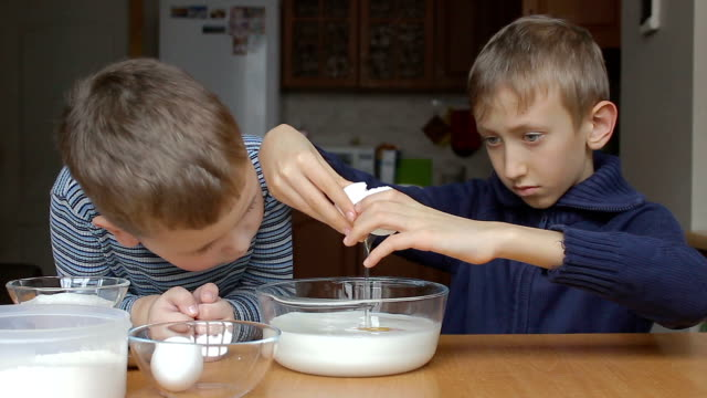 Boys prepare the dough and the older boy adds eggs to the milk video