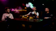 Boys smoking hookah in the lounge caffee. Slow motion video