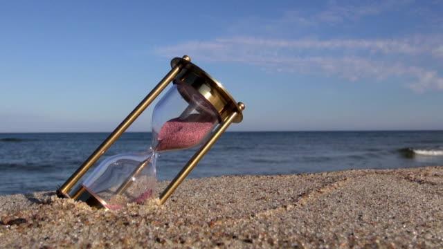 brass ancient hourglass sandglass clock on sea beach sand video