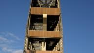 Brave tourist people walking on transparent floor high in sky on observation tower. Tilt up. video