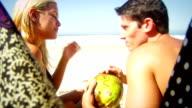 Brazilian couple sit on a beach drinking fresh Coconut water video