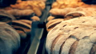 Bread, buns and other bakery products of golden color on store shelves video