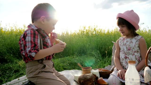 Bread in baby's hands, girl treats boy piece of bread glass of milk in backlight, Children grimace, Slow motion in Backlight video