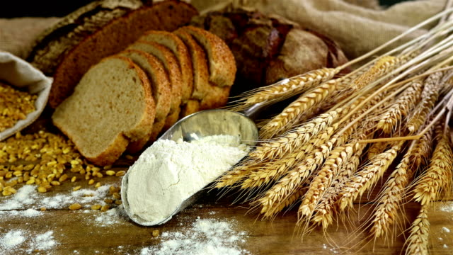 Bread, sheaf of wheat ears and flour  on a wooden table, dolly video