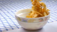 Breakfast cereal crunchy corn flakes falling into bowl in slow motion video