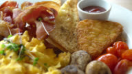 Breakfast dish with egg , bacon , sausage , bread and other video