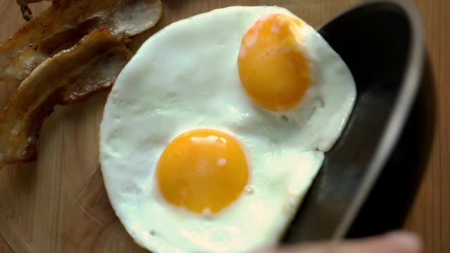 Breakfast of coffee, bacon and eggs on a wooden table. Top view video