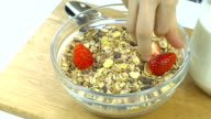 Breakfast, put fresh strawberries in cereal bowl, slow video