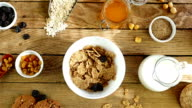 Breakfast scene top view, cereal, dried cherries and hazelnuts are poured into a bowl video