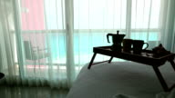 Breakfast wooden tray with coffee percolator and cups on bed at hotel room with ocean view video