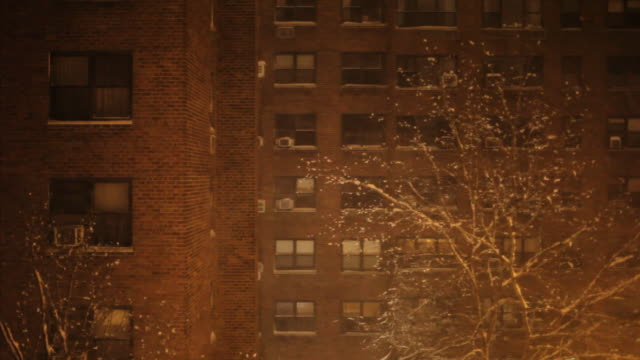 brick apartment building in snow - night video