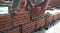 Bricklayer worker installing brick masonry on exterior wall video