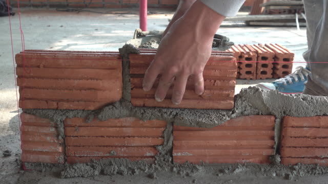 Bricklayer worker installing brick masonry on exterior wall video