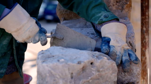 Bricklayer's hands placing lime with a trowel video