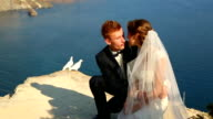 bride and groom and white pigeons on coast of beautiful mountain culver video