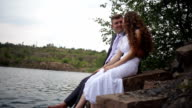 bride and groom are sitting on the shore of the lake video