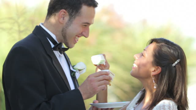 Bride and groom at wedding feed each other cake video