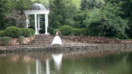 Bride and groom by pond in the park video