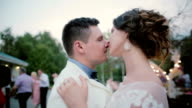 Bride and groom dancing first dance on their wedding. Man and woman turn and sing outdoors, have a good time in nature video