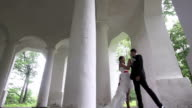 Bride and groom dancing in the ancient columns. video