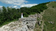bride and groom kissing on the rock. video