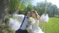 POV Bride and groom kissing on the swing in sunshine video