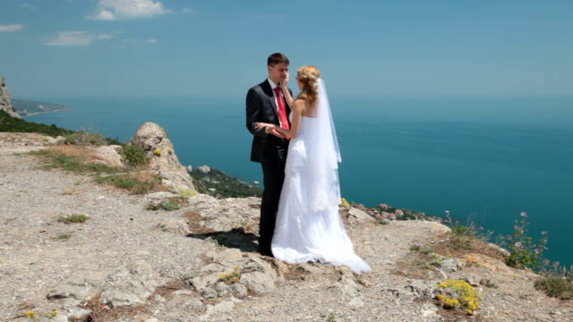bride and groom on a cliff against blue sky video