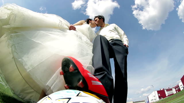 Bride and groom on the football field, a gentle kiss video