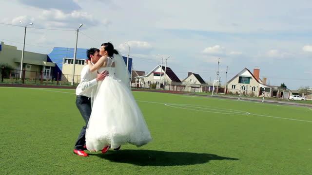 Bride and groom on the football field, loving feelings video
