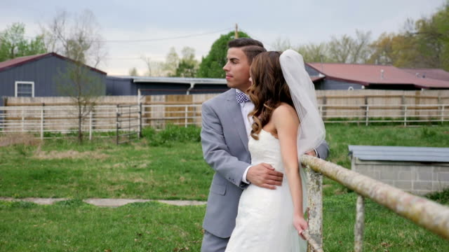 Bride and Groom pose for pictures along old metal fence video
