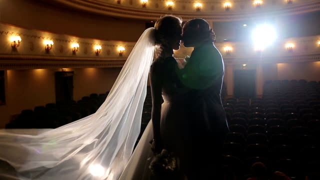 Bride and groom pose on stage theater backlit silhouette. Bride and groom stand embrace kiss in empty opera hall. Theatrical performance on marriage relationship. Gender equality. Wedding veil dress video