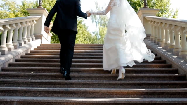Bride and groom run up the stone stairs video