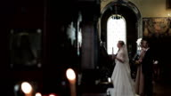 Bride and groom stand with candle at wedding ceremony in orthodox church in Nice France. Best man and maid of honor bless crossing behind betrothed. Greek orthodox church ritual traditions and customs video