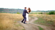 bride and groom walking along the road in a field video