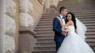 Bride and groom walking in park, kissing video