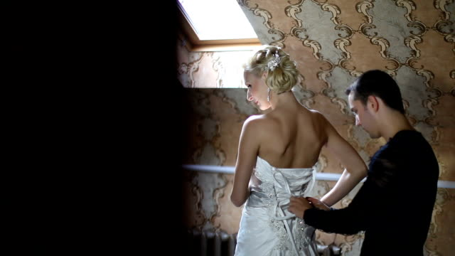 Bride dresses before a mirror, it helps her fiance video