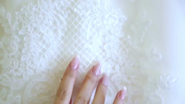 bride gently fingers on a wedding dress video