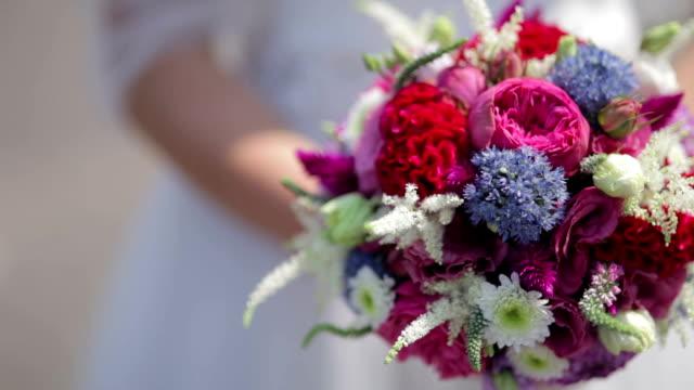 CLOSE UP PANNING SELECTIVE FOCUS Bride holding colorful bouquet video