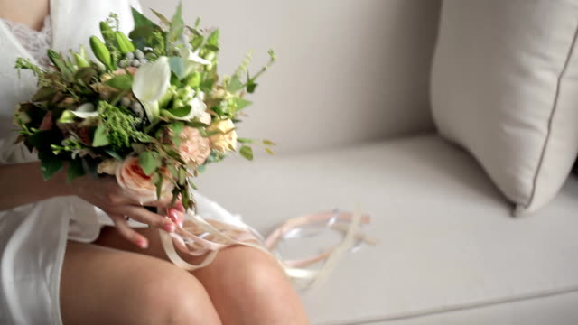 Bride holds beautiful small bouquet with flamingo ribbons video